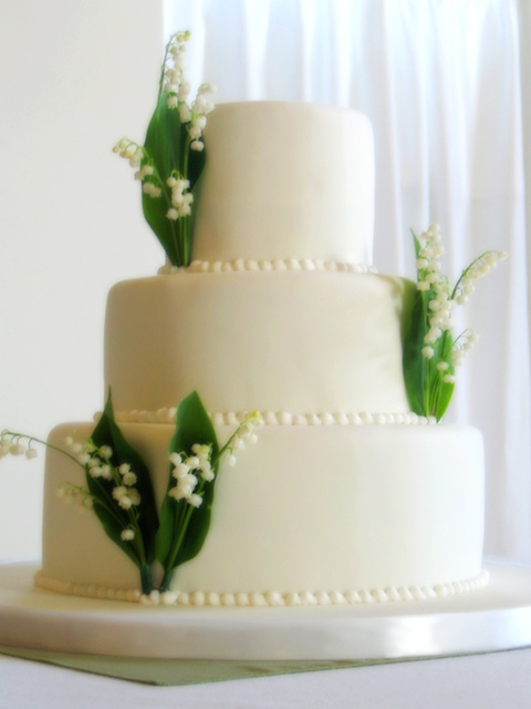 Three-tier butter cake with handmade rolled fondant and fresh flowers